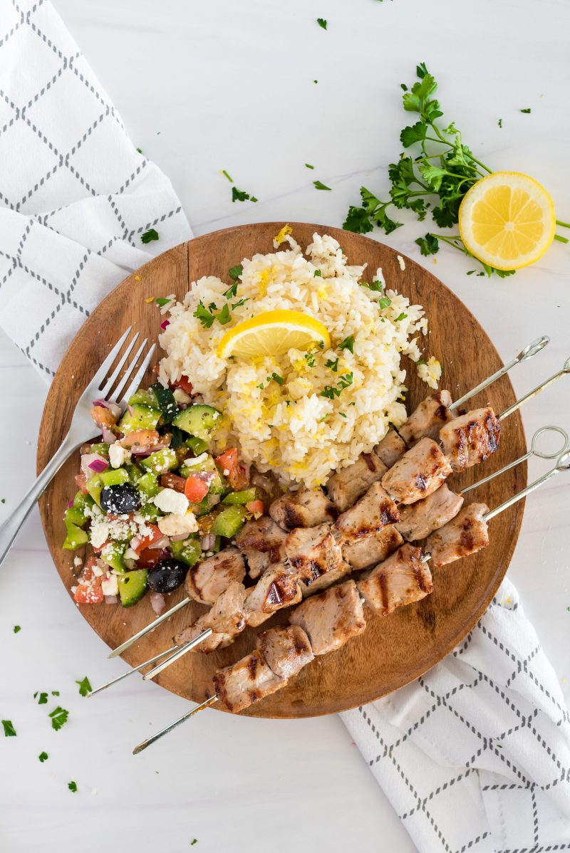 overhead of a wooden plate with lemon rice, chicken skewers and chopped salad