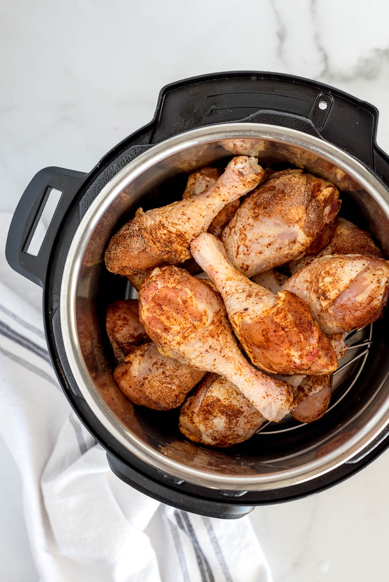 An overhead shot looking down into an Instant Pot filled with chicken legs that are covered in spices