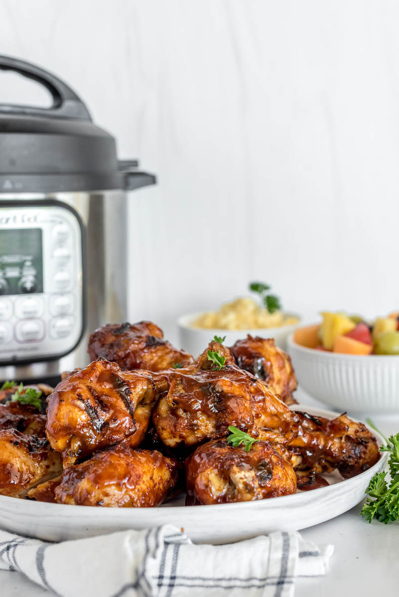 A photo of a white round plate of cooked BBQ chicken legs, with an Instant Pot and a bowl of fruit salad in the background
