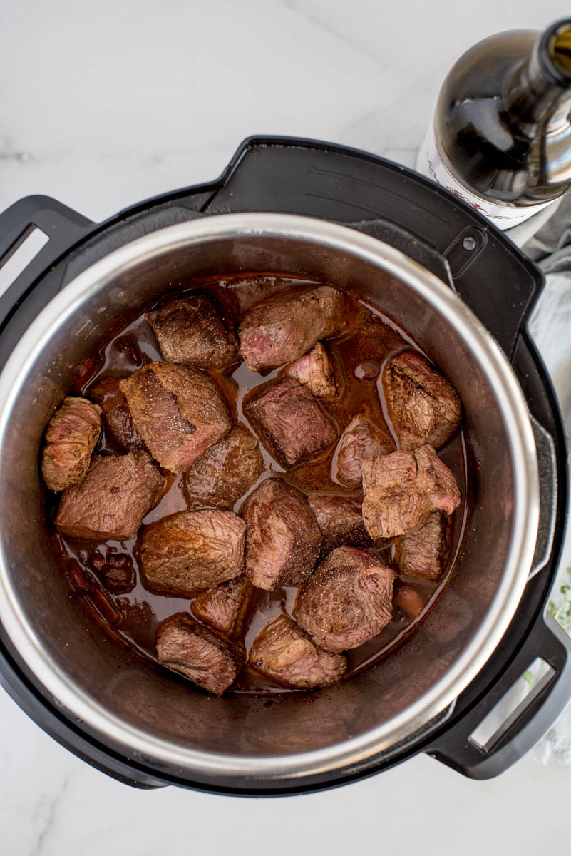 The browned beef and cooking liquid in the Instant Pot ready to be cooked fork tender.