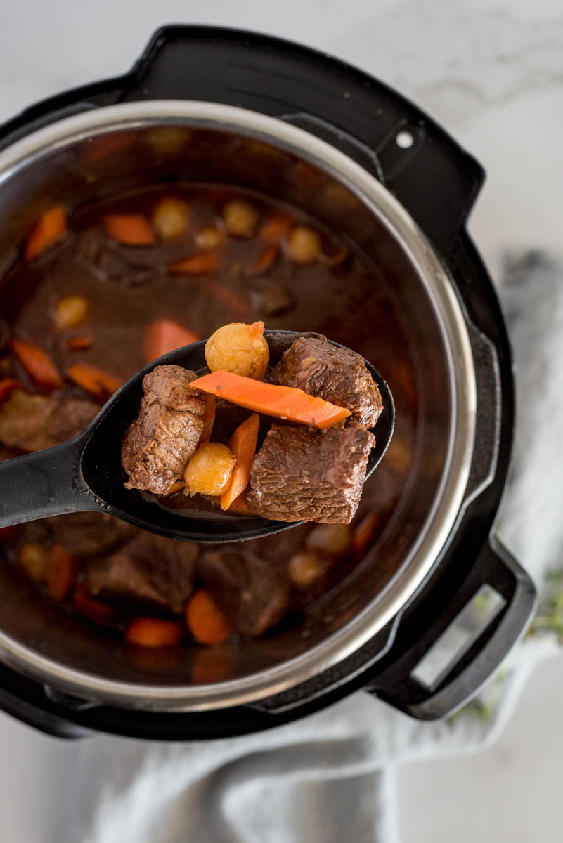 Beef bourguignon cooked in an Instant Pot with the beef, carrots and pearl onions on a spoon.