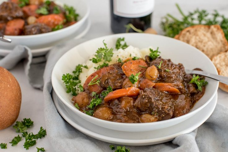 Close up picture of Instant Pot beef bourguignon served with mashed potatoes and fresh parsley in a white bowl with rolls and a bottle of red wine in the background.