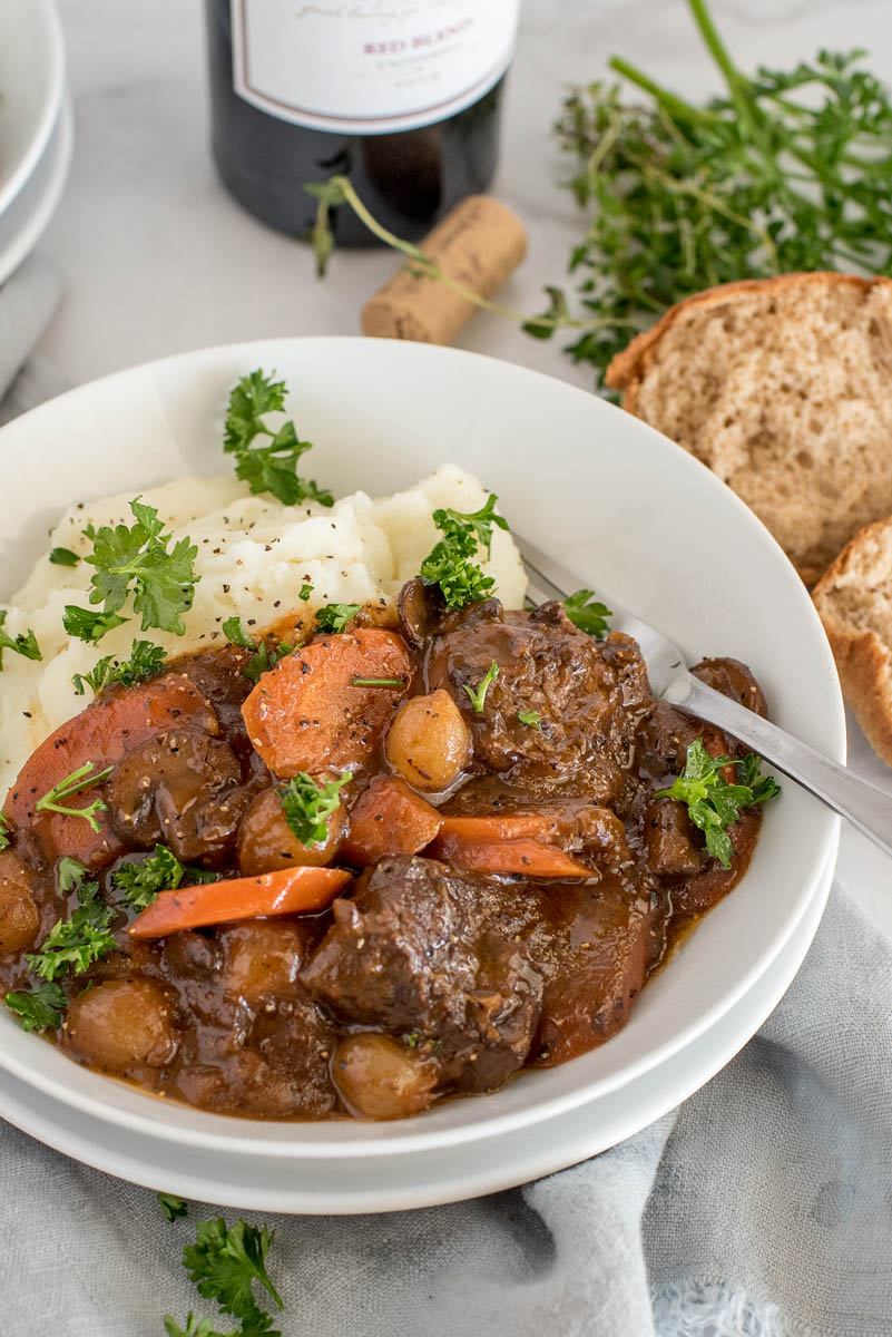 Close up picture of Instant Pot beef bourguignon cooked with carrots and pearl onions, served with mashed potatoes and fresh parsley. With rolls and a bottle of red wine in the background.