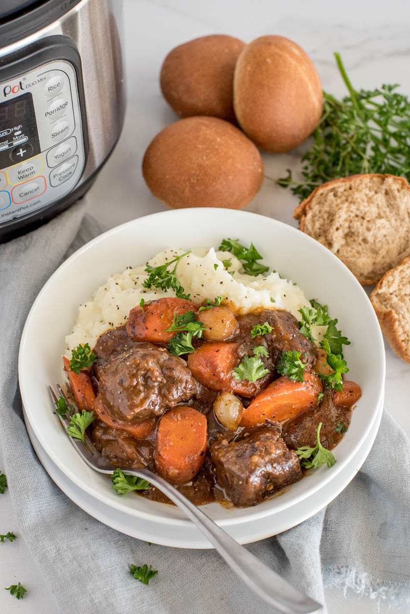 Overhead picture of beef bourguignon served in a white bowl with mashed potatoes and fresh parsley with an Instant Pot and rolls in the background.