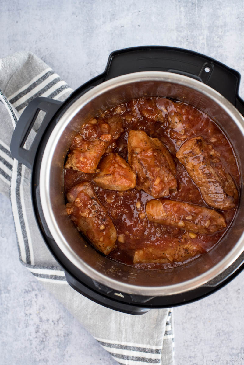 pressure cooker with pork ribs in sacue