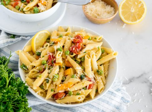 bowl of instant pot pasta primavera with fresh vegetables and parmesan cheese on top