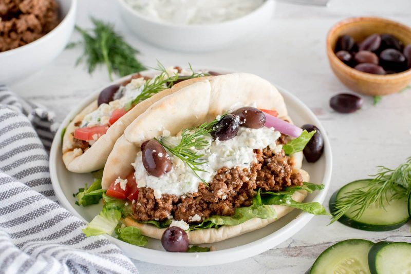 plate with two greek beef tacos topped with tzatziki sauce, olives, cucumbers and dill