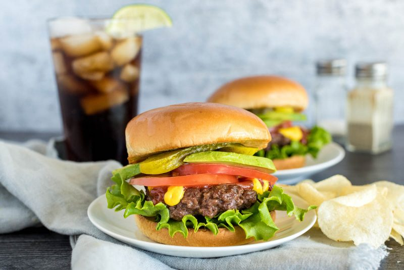 onion burgers on buns with toppings in front of a glass of soda