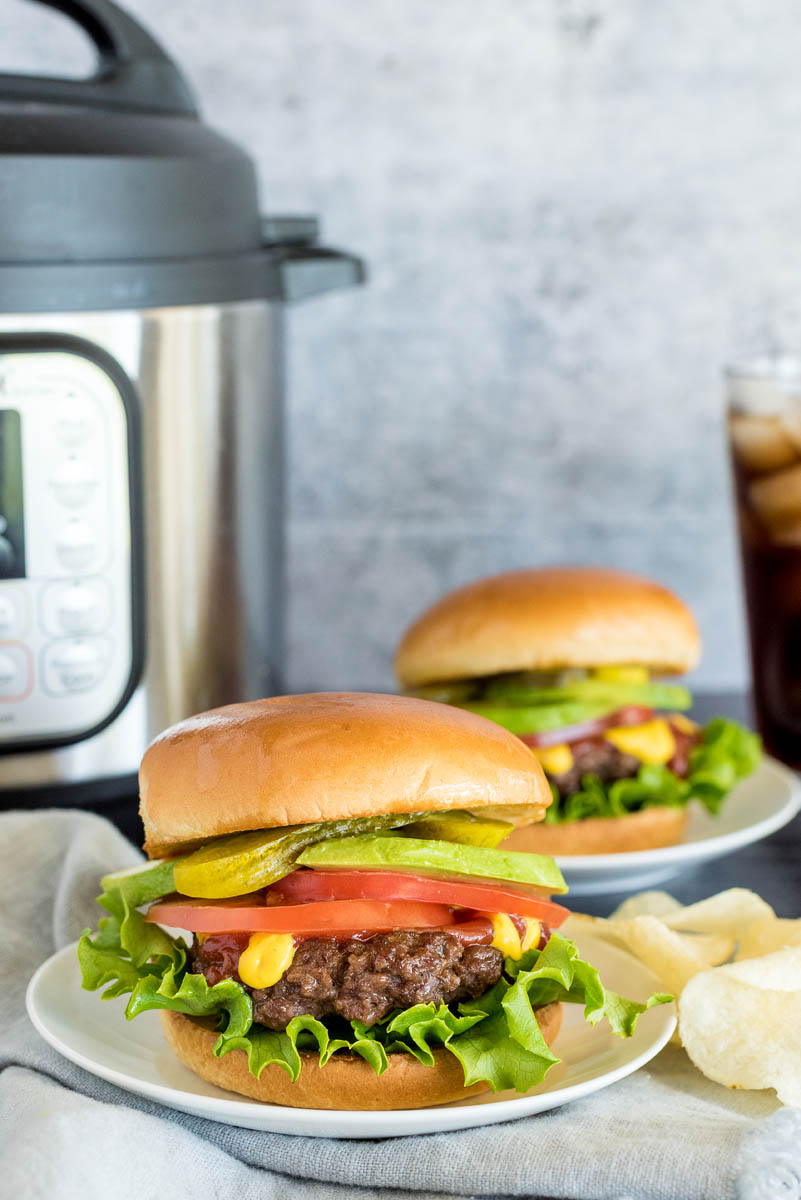 two onion burgers with toppings in front of an instant pot pressure cooker
