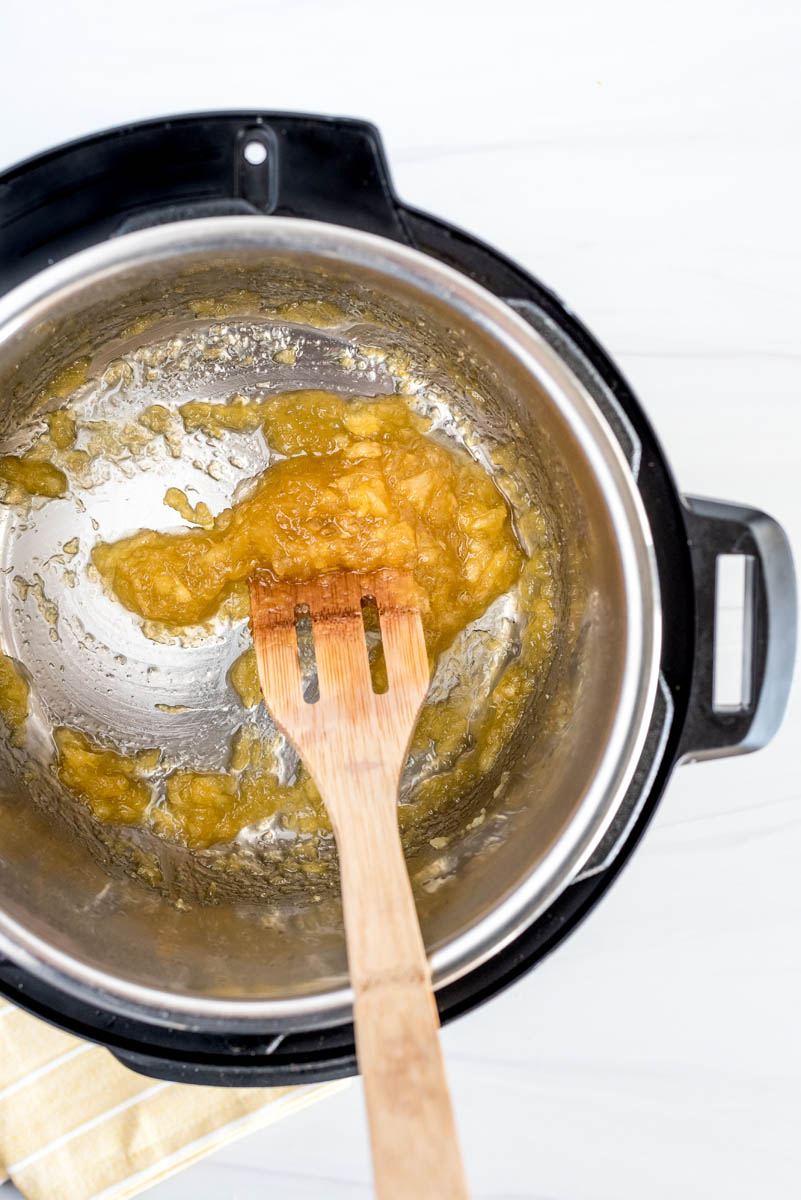 An overhead shot of the pineapple sauce stirring around by a wooden spoon