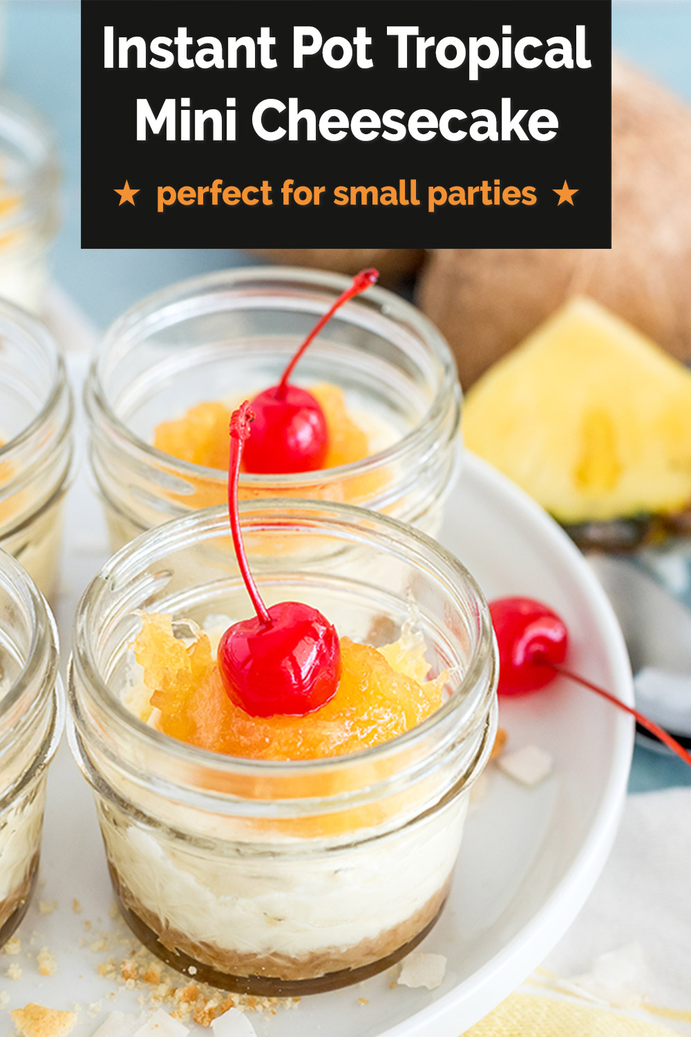 """A Pinterest image that reads """"Instant Pot Tropical Mini Cheesecakes: perfect for small parties"""" overlaid on a close-up image of two mini mason jars filled with coconut cheesecake, pineapple topping, and a maraschino cherry with a pineapple wedge and a coconut in the background via @PressureCook2da"""