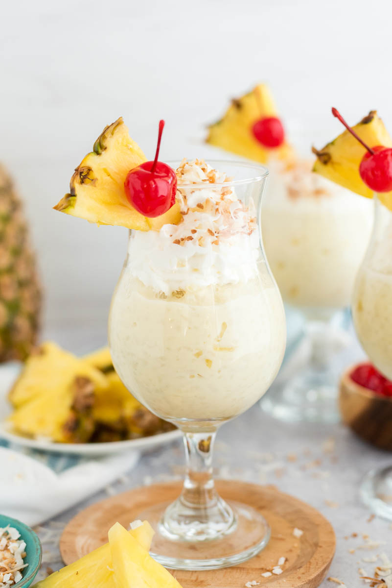 several glasses of coconut pudding with fresh fruit and whipped cream on top