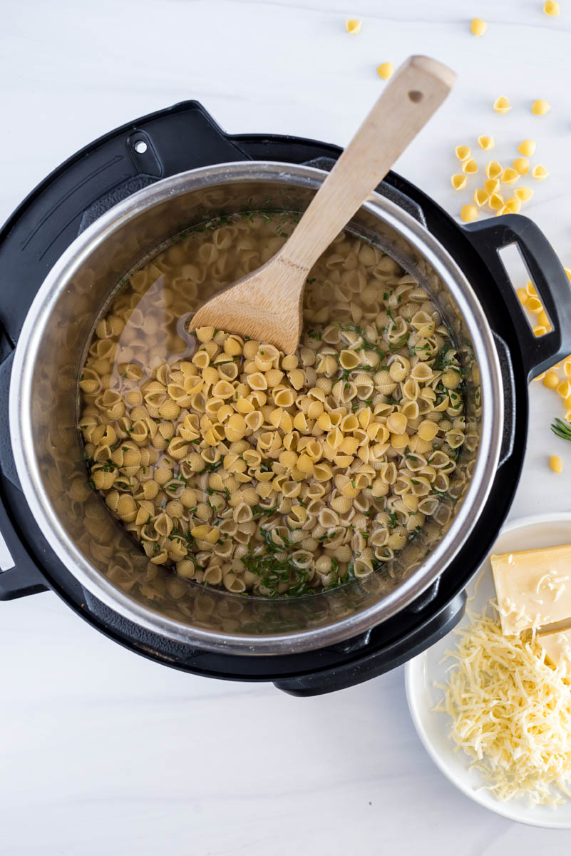 overhead of an instant pot with uncooked bacon mac and cheese