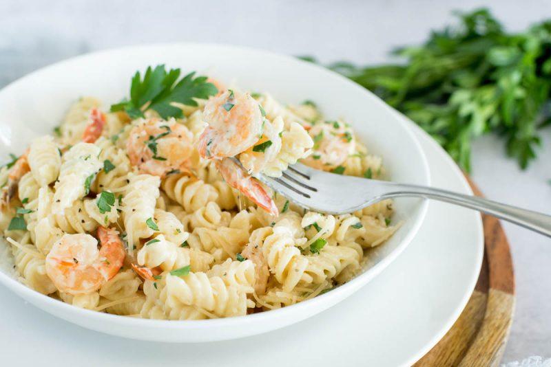 white bowl of instant pot shrimp alfredo rotini with parsley