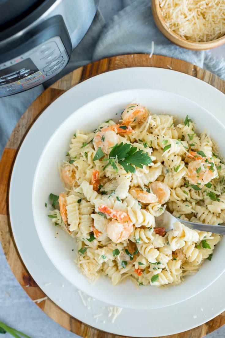 white bowl of instant pot shrimp alfredo rotini pasta