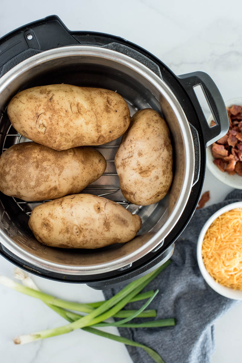 overhead of an instant pot with four russet potatoes inside on a wire rack or trivet