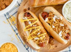 Overhead close up shot of two hot dogs topped with Instant Pot chili dog sauce, garnished with mustard, onions, and cheese