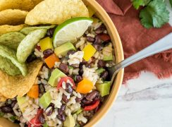 close up on a bowl of brown rice and black bean salad wth tortilla chips and lime