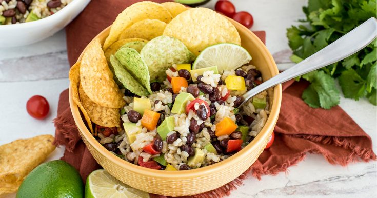 bowl of rice and bean salad with chips and lime juice