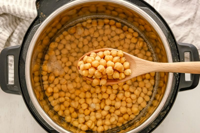 spoon holding cooked chickpeas over an instant pot