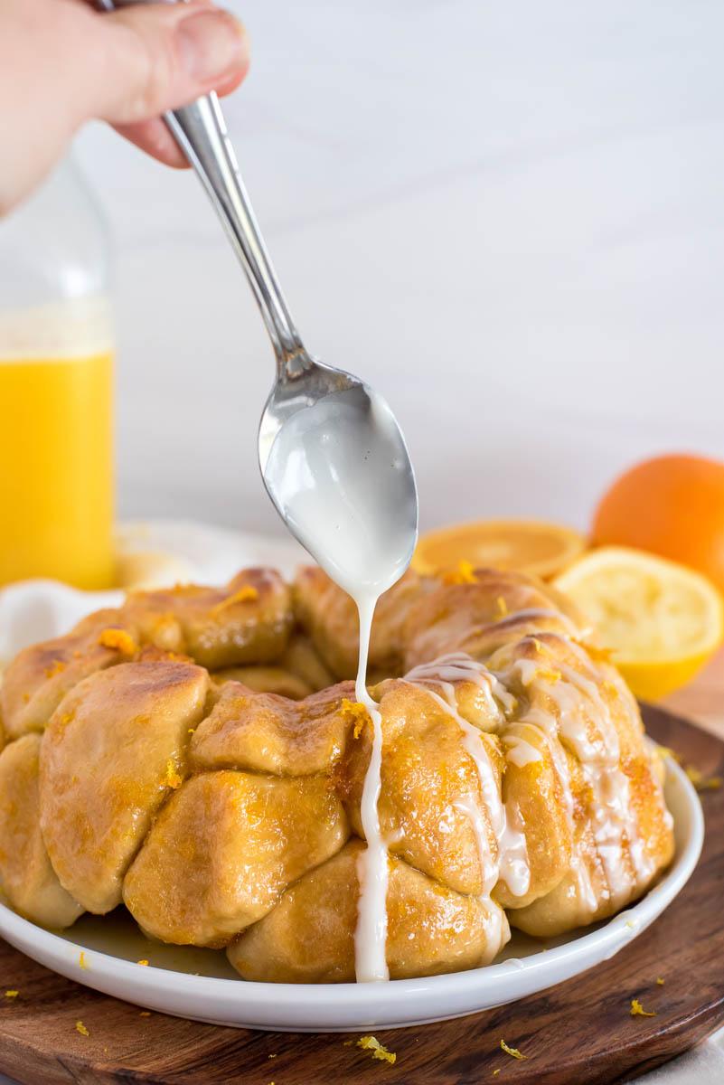pouring citrus glaze over instant pot monkey bread