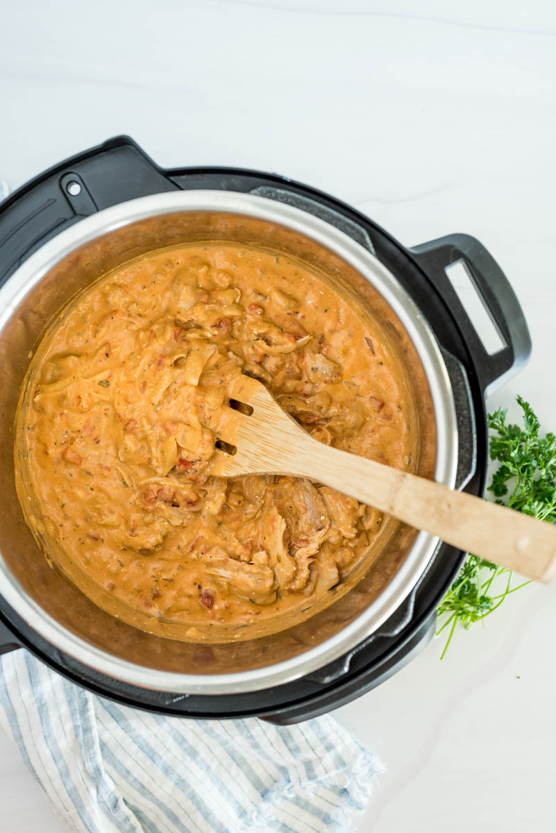 Paprika chicken cooked in an Instant Pot with a wooden spoon to serve.