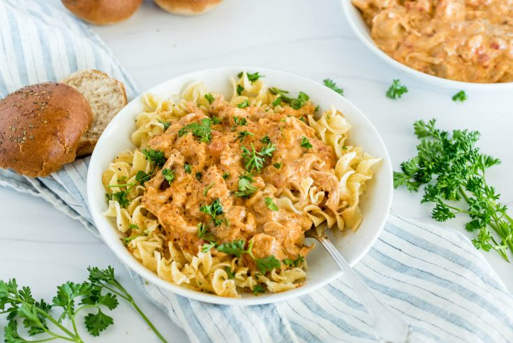 A bowl of Instant Pot paprika chicken made from frozen chicken, and ready to eat served on top of egg noodles with fresh parsley on top.
