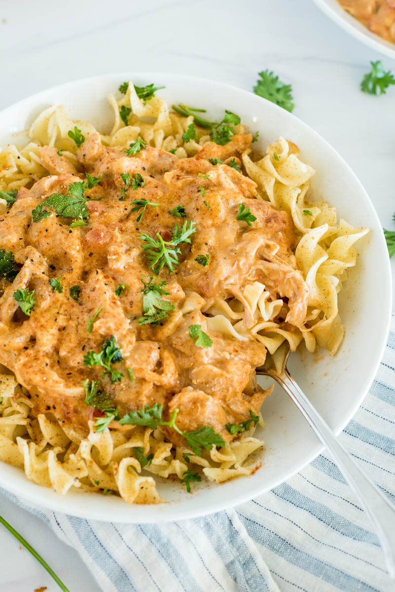 Close up of paprika chicken made in an Instant Pot and served over egg noodles with fresh parsley on top.
