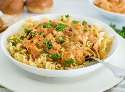 Close up picture of Instant Pot paprika chicken served over egg noodles with fresh parsley on top.