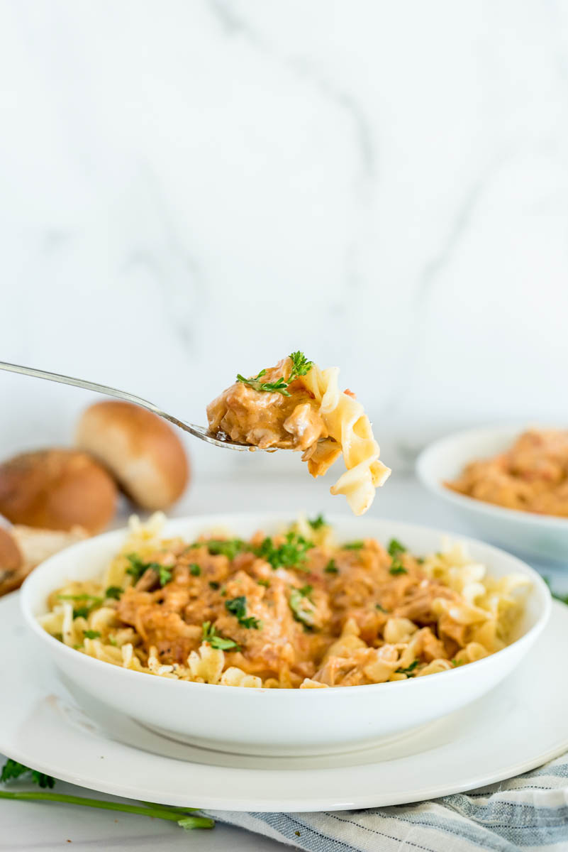 Instant Pot paprika chicken served in a bowl with egg noodles with a bite on a fork, ready to eat.