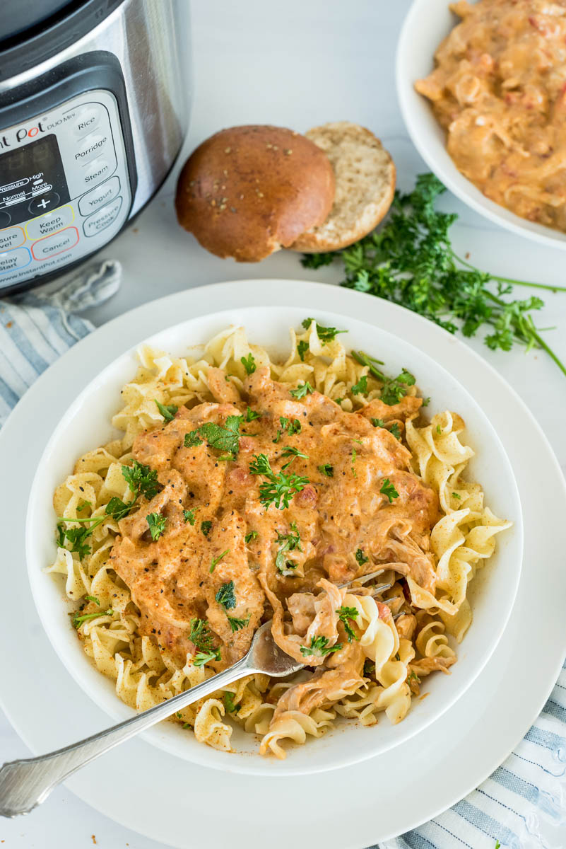 Overhead shot of pressure cooker paprika chicken served over egg noodles and served with fresh parsley, placed in front of an Instant Pot.