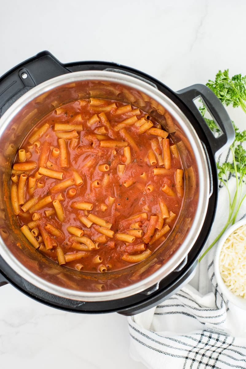 An overhead shot looking into an Instant Pot filled with cooked ziti and marinara sauce, before adding the alfredo sauce