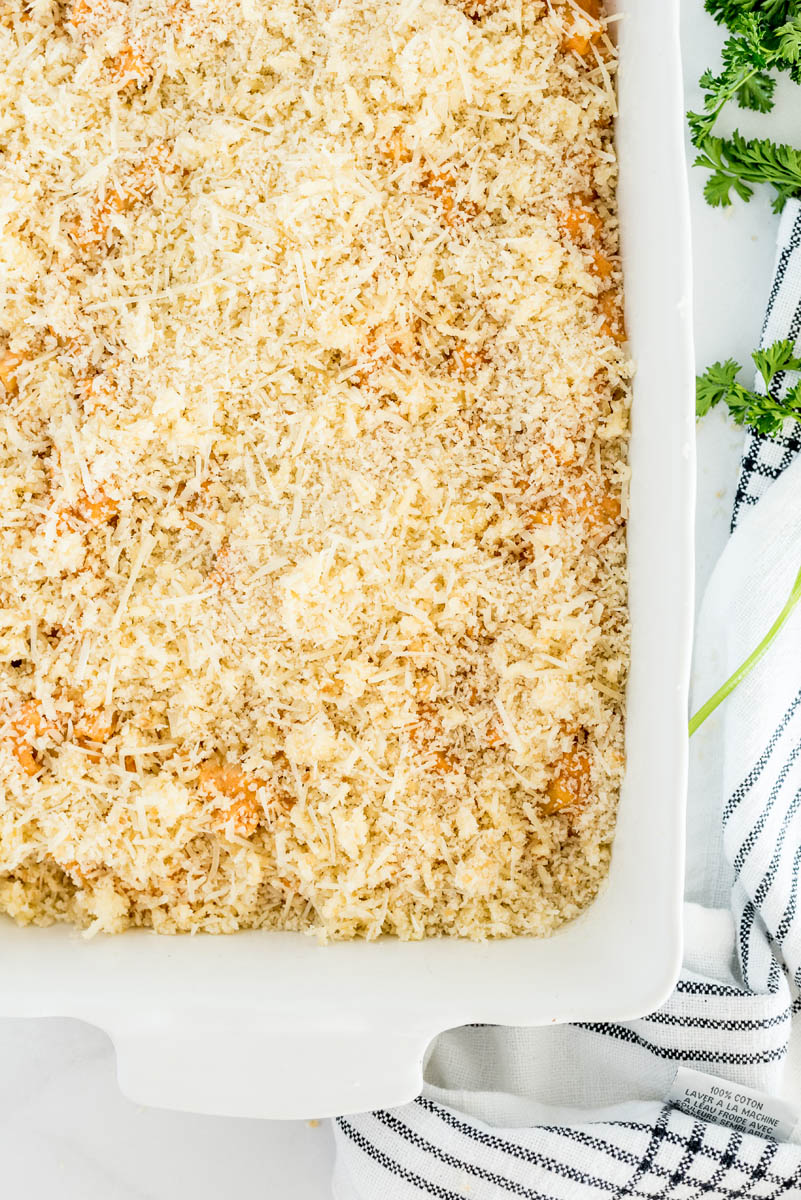 An overhead shot of the baked ziti topped with breadcrumbs before browning