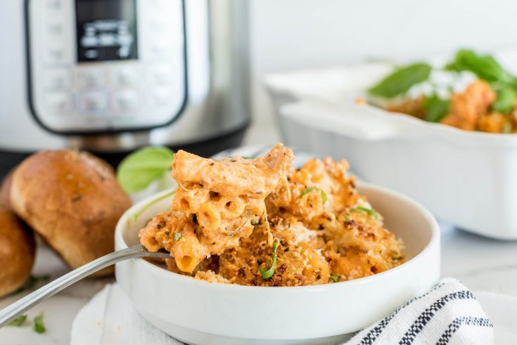 A horizontal shot of a small white bowl filled with cooked ziti and a spoon, sitting in front of an Instant Pot and several rolls