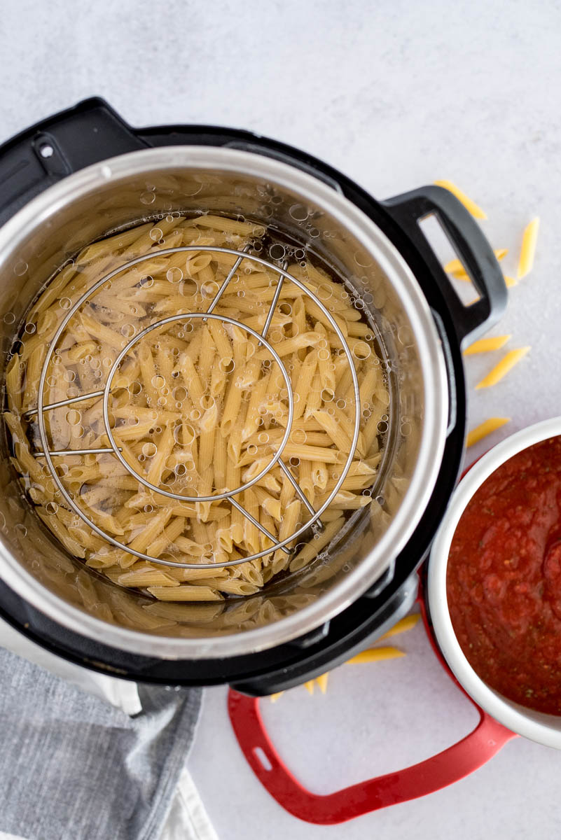 An overhead photo of the Instant Pot with the pasta and trivet inside and the tomato sauce in the silver cake pan, ready to sit on top of the trivet