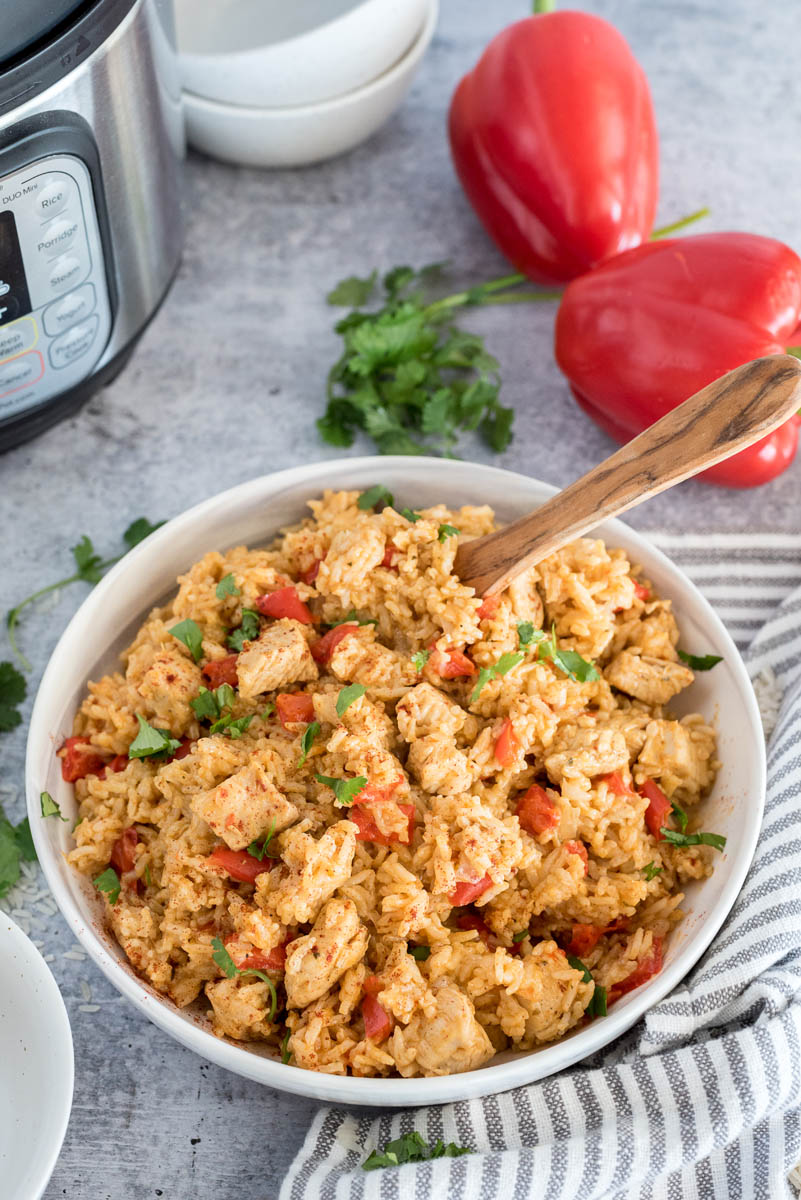 45 degree shot of a white bowl full of Instant Pot spanish style chicken and rice, with an instant pot, bell peppers, and cilantro in the background