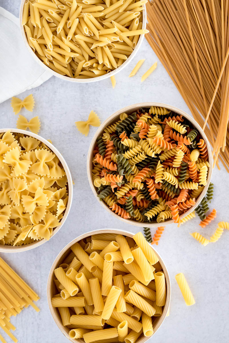 Multiple types of uncooked pastas in different bowls. This tutorial will tell you how to cook any of these kinds in an Instant Pot