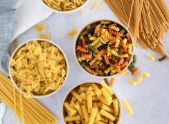 Overhead shot on three white bowls of pasta filled with bow ties, rotini, and penne pasta arranged in a triangular shape, with fettuccini and spaghetti in the corners