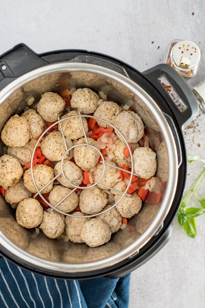 frozen meatballs in an instant pot with marinara sauce and a trivet
