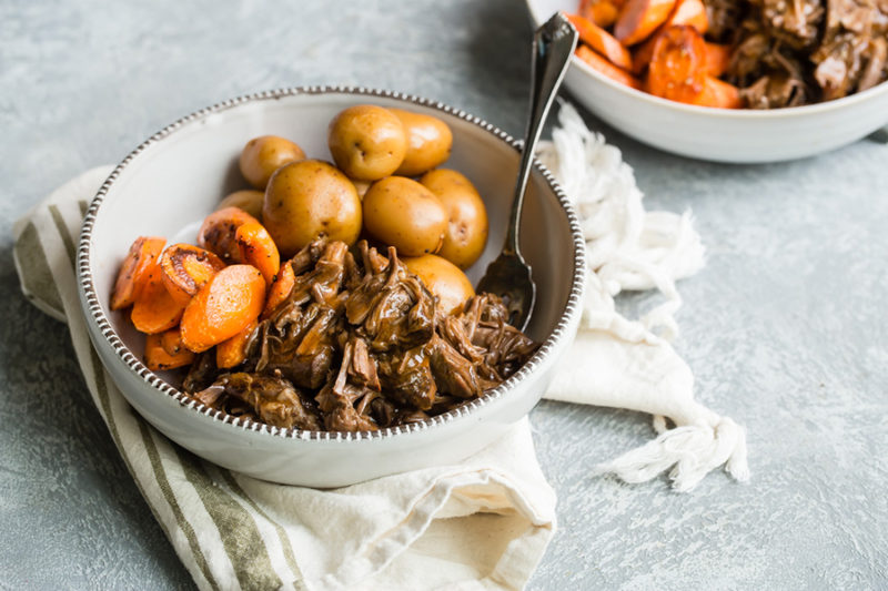 Instant Pot Pot Roast. potatoes and carrots served in a white bowl with fork