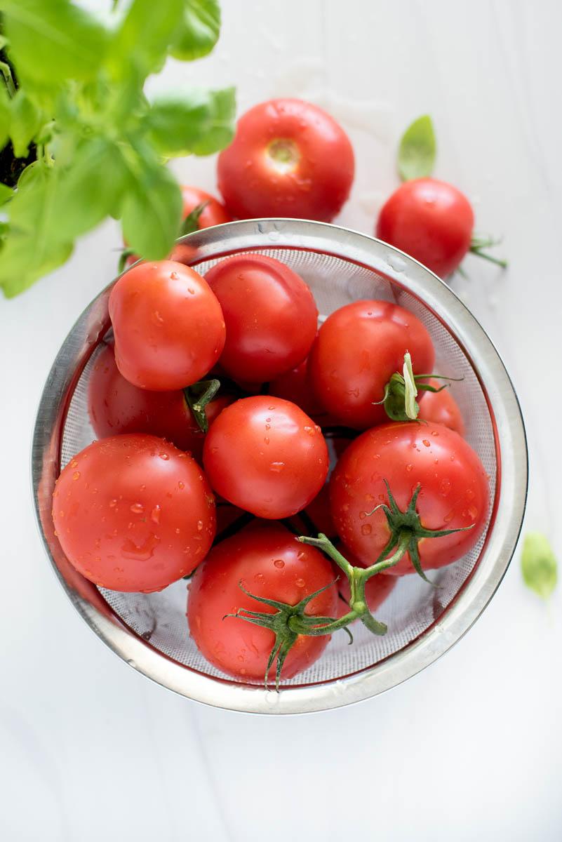 an overhead shot of a collander full of fresh garden tomatoes