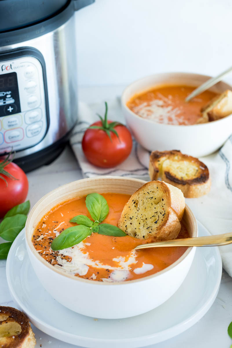 A 45 degree image of a white bowl filled with tomato basil soup, with an Instant Pot and fresh tomatoes in the background