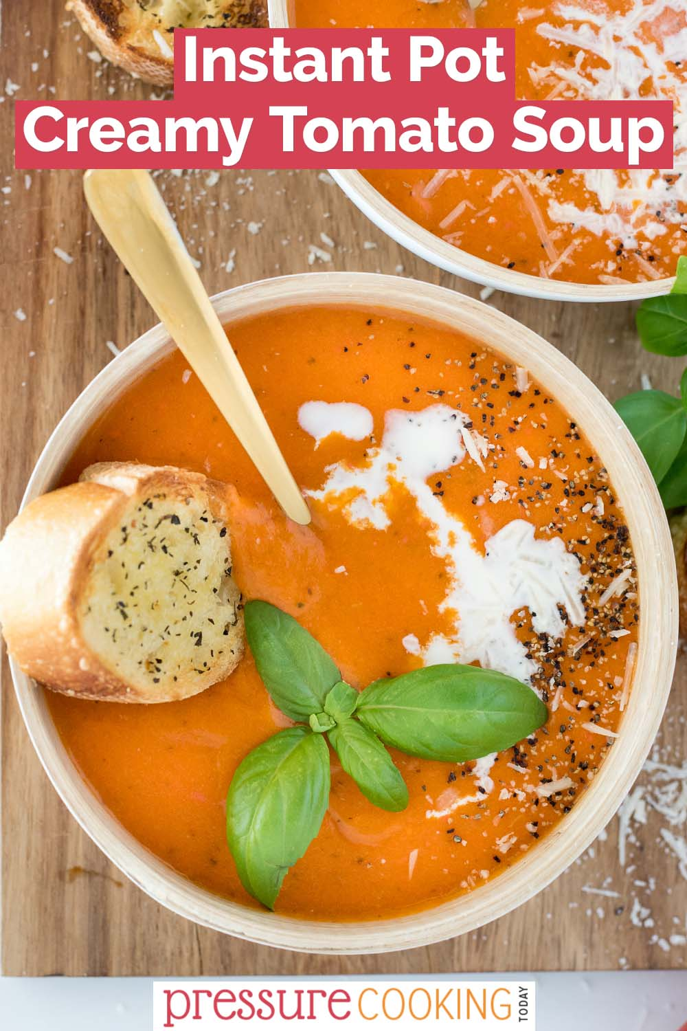 pinterest button promoting Instant Pot Creamy Tomato Soup, with an overhead shot into a white bowl against a wooden background, filled with creamy orange soup, a baguette slice, and a basil garnish via @PressureCook2da