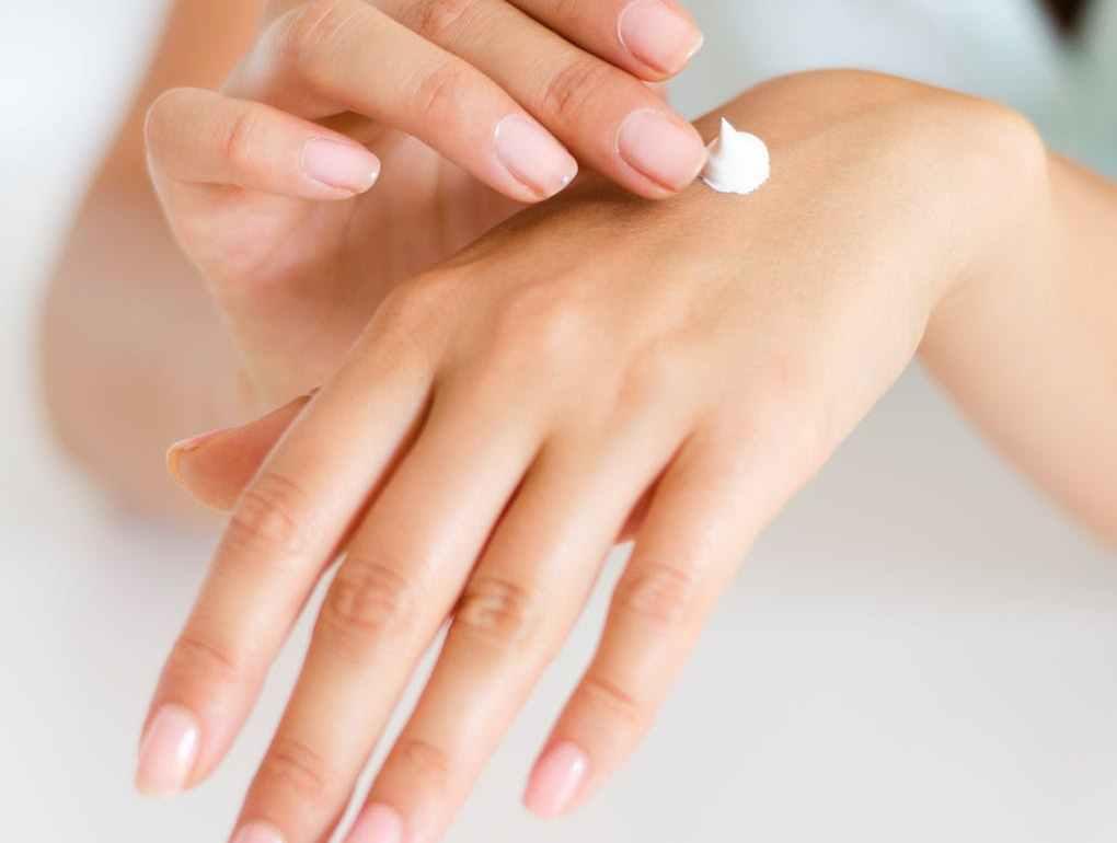 woman applying lotion on hand