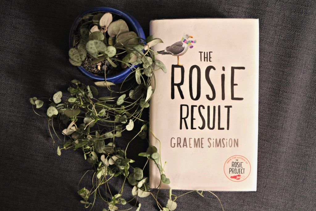 This picture is of the front cover of The Rosie Result.  It is plain white with black text and a seagull with a scarf on it.  The Rosie Result by Graeme Simsion Book Review.