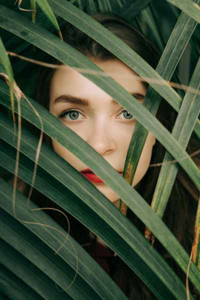 woman in red lipstick hiding behind green leaves