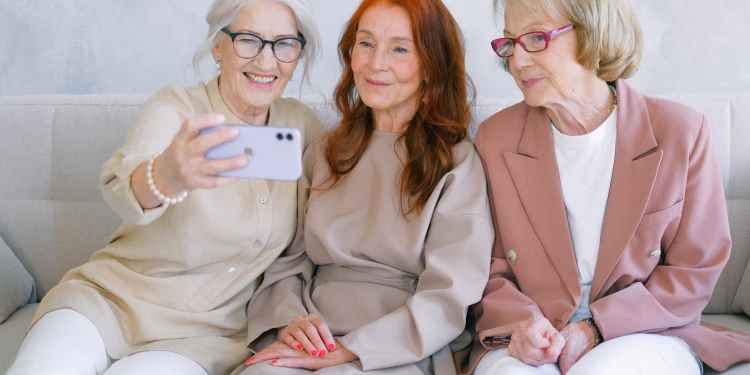 aged happy women making video call online on smartphone