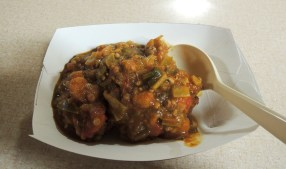 A closeup of fritters in a spicy shrimp-okra sauce.
