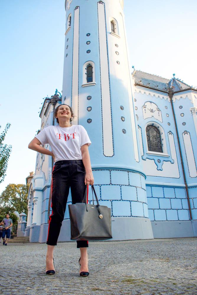 žena stojaca pred Modrým kostolom v tričku, nohaviciach a lodičkách
