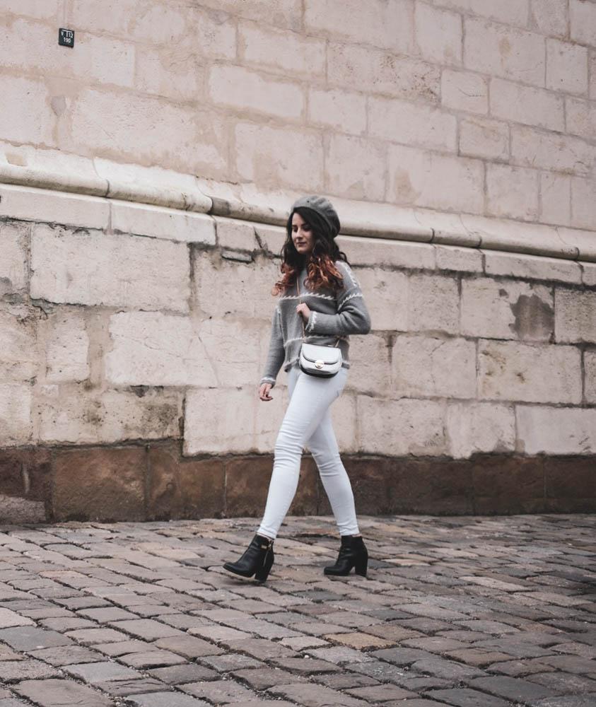 žena v sivom pulovri, bielych rifliach a čiernych členkových čižmách so striebornou mini kabelkou na pleci a baretkou na hlave